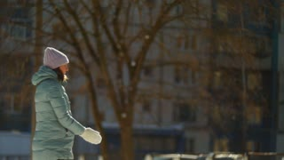SLOW MOTION: Happy young woman playing with snow