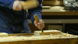 Wood carving - Human hands chiseling a piece of wood.