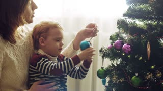 Young mother with her baby boy are decorates a Christmas tree