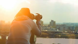Woman looks in binocular viewer at cityscape. Sunset evening view