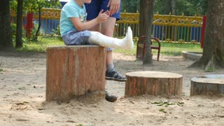 Young boy with broken leg is sitting in park