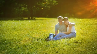 Young couple sitting on grass in summer park and dreaming about they own house. Symbol of mortgage drawing behind them