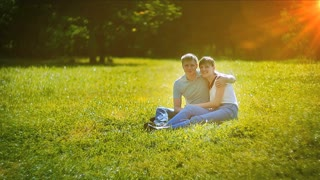 Young couple sitting on grass in summer park
