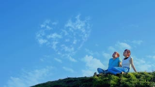 Young couple sitting on the hill and dreaming about love and family