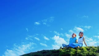 Young couple sitting on the hill and dreaming about sea travel vacation