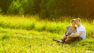 Young happy couple sitting on green grass in park and dreaming about they own house. Mortgage concept.