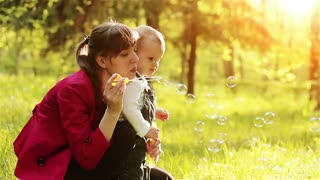 Young mother and her two years old baby boy playing in park with soap bubbles.