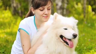Young woman hugging her big white dog on bright park background