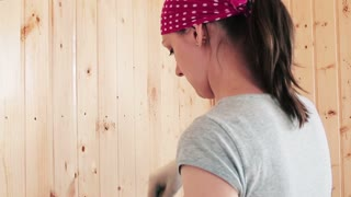 Young woman painting the wooden wall.
