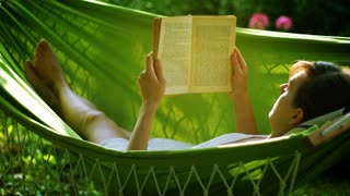 Young woman reading book lying on hammock on backyard.