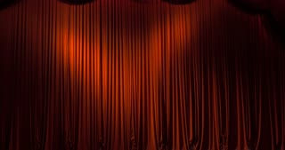 A closed red stage curtain in a theater