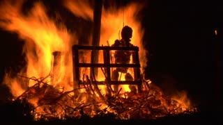 A puppet of an old witch is burnt on a bonfire