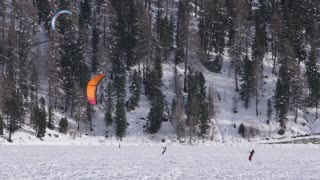 A snowkiter trying to lift his kite on a frozen lake in the Switzerland Alps