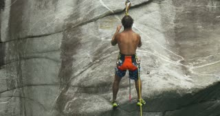 A young athlete climbs on the wall of a canyon during the