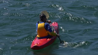 Athletic man kayaking in trouble waters
