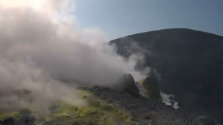 Tourists walking on an edge of volcano crater