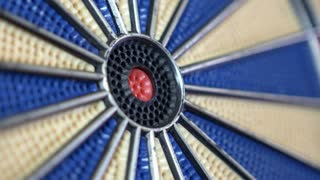 4K close-up footage of a dart board and a person hitting the bullseye...