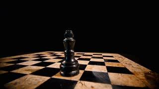 4K footage of a chess board on a black background with a black king on it, a white king hits the black and stands on his place...