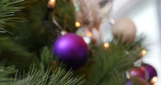 4K footage of a person decorating a Christmas tree with a purple ball...