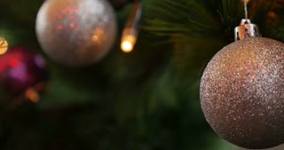 4K shot of a Christmas tree and a white ball in the front-the shot goes out of focus...
