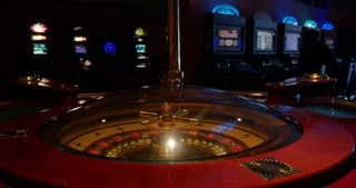 A 4k wide shot of a casino roulette in the foreground and some slot machines in the background