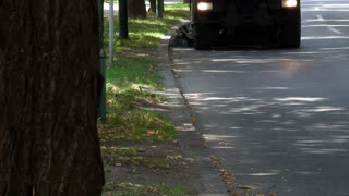A utility company´s road cleaning truck passes by and cleans the street...