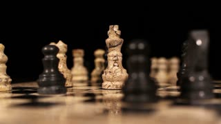 A black bishop hits the white king piece and it falls down on the chess board...