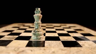 A black king hits a white king on an empty chess board, isolated on black background...