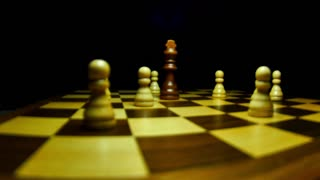 A black king surrounded by white pawns on a chess board, a man picks the black king and lies it on the board...