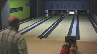 A bowling player at a recreational club throwing the ball in hope to hit all the skittles...