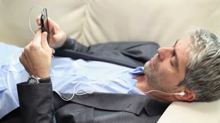 A businessman relaxing on a couch and listening to music...