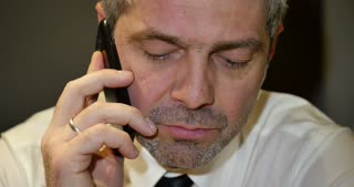 A businessman talking on his mobile phone, receives bad news and starts to shout at somebody