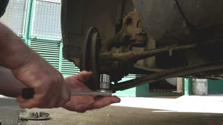 A car mechanic changing a part of the car, footage with voice of the screw driver...