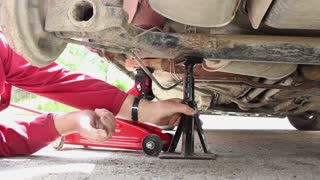 A car mechanic jacking up a car in order to replace the disc brake pads...