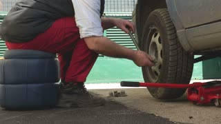 A car mechanic taking of a car´s tire so he can change a broken part...