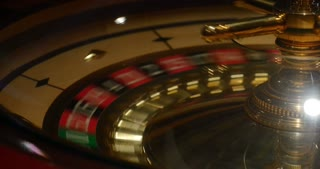 A casino roulette in motion, the ball is spined and it stops at a red number