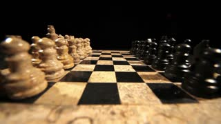 A chess board and it´s figures lined up for a new game start and a man making his first move with a black pawn...