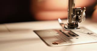 A close up shot of a sewing machine, a person is sewing a black material