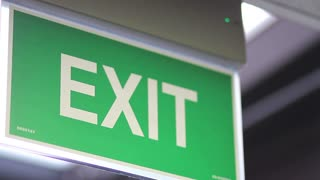 A close up shot of an emergency exit sign which goes into focus and out of focus