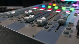 A colorful audio mixer, the knobs are being pulled automatically up and down...