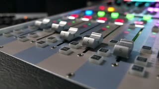 A colorful audio mixer, the knobs are being pulled automatically up and down, the shot is moving from right to left and vice versa...
