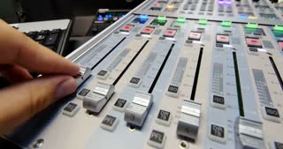 A colorful audio mixer, the knobs are being pulled up by a man, the shot is moving from left to right on a slider...