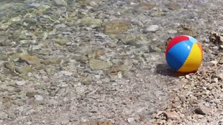 A colorful ball floating in the water at a beach...