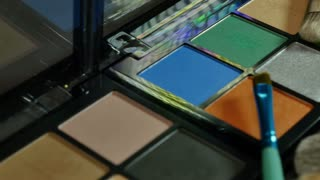A colorful make-up palette and some brushes lying around it, the shot is moving...