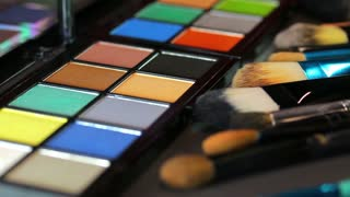 A colorful make-up palette with some brushes lying in front of it and a make up artist using a color from the palette...