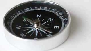 A compass lying on a white table and goes crazy...