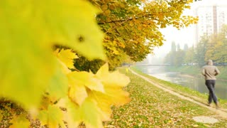 A fall scene with colorful leaves, and a man enjoying jogging in the nature...