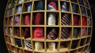 A fish-eye front shot of a tie collection and a man picking up a tie for his shirt...