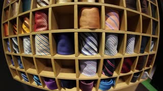 A fish-eye front shot of a tie collection and a man picking up a tie for his shirt