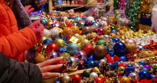 A girl buying some colorful christmas tree balls on a christmas market